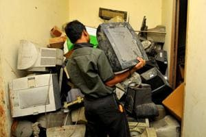 A person disposes of e-waste at a scrap dealer's place in Noida.