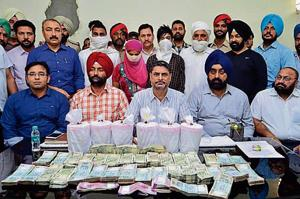 Special task force members along with other officials showing the recovered cash and heroin in Amritsar.
