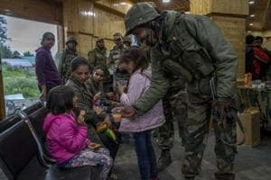 An army soldier offers juice to a child after she was rescued from a cable car in Gulmarg, Kashmir, in June 2017. The army was called in to help with rescue efforts after a cable car came crashing down from a height of at least 100 feet in the tourist resort of Gulmarg, leaving scores of tourists stranded.