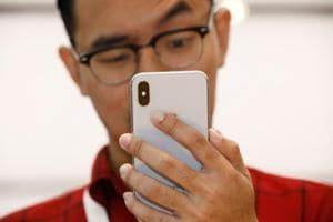 A man tries out the Animoji feature on an iPhone X during its launch at the Apple store in Singapore. REUTERS/Edgar Su
