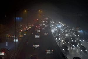 Vehicles ply at a slow pace near Punjabi Bagh due to low visibility caused by air pollution in New Delhi on Tuesday.