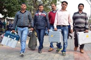 Polling officers carry EVMs ahead of the election in Dharamsala in Himachal Pradesh. (Shyam Sharma / HTPhoto)