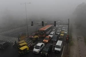 Commuters drive amid heavy smog in New Delhi.