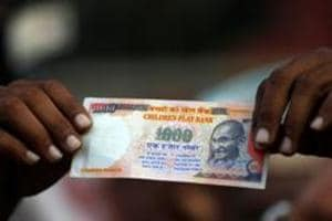 A demonstrator shows an old fake 1000 rupee note during a protest, organised by Congress, to mark a year since demonetisation was implemented by Prime Minister Narendra Modi, in Ahmedabad, November 8.