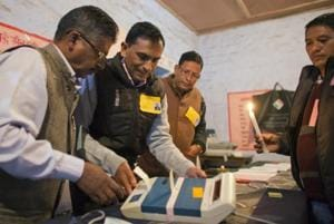 Election officials prepare an electronic voting machine at a polling station in Dharmsala, on Nov. 9, 2017.