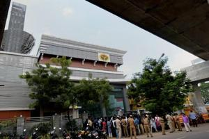 Media persons stand in front of the Jaya TV office where Income Tax officials conducted a raid in Chennai on Thursday. Jaya TV is run by the family of jailed AIADMK leader VK Sasikala.