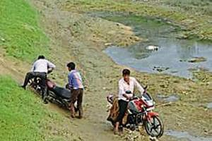 Locals struggle to cross the dry river bed with their motorcycles in Uttar Pradesh's Birahimpur village.