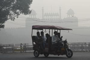 A battery run tricylce rickshaw passes by the Red Fort amid heavy smog in Delhi. Large swathes of India