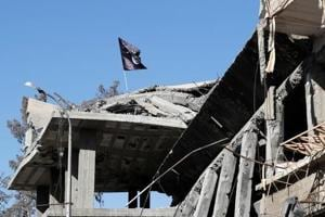 An Islamic State flag flutters atop a bombed house in Raqqa, Syria. The militant group is on the backfoot, following sustained attacks by Iraqi troops and US-backed militias.