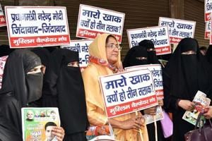 """BJP supporters in the Muslim community hold placards against the triple talaq practice during an election campaign in New Delhi. While some appreciate the saffron party for  appropriating the issue, others believe it has """"interfered with the community's faith""""."""