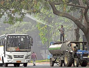An NDMC worker sprays water on a tree to settle dust as part of the measure against pollution, in New Delhi on Monday.  Delhi fire services on Wednesday followed the order by sprinkling water from Vikas Minar at ITO. The spraying, which was started around 4pm, was done for nearly an hour.