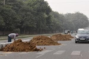 Workers leave sand uncovered while constructing a median on a road in sector 45-46, on Tuesday.
