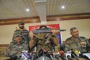 Inspector general of police Muneer Khan displays an AK-47 Draco rifle during a joint press conference with Army and CRPF officers recently.