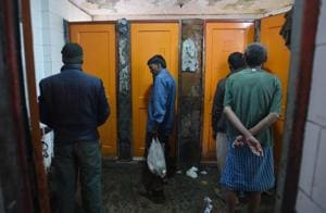 People wait outside a toilet at the Lahori Gate night shelter in New Delhi on Saturday.