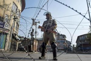 A security jawan stands guard during restrictions in Srinagar.