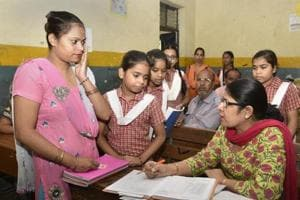 A teacher (R) in a Delhi government school with a parent at a special meeting.