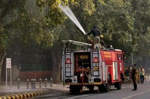 A firefighter sprays water on trees as part of the anti-pollution measures to improve air quality in Delhi on Thursday.