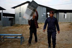 A man carries ballot boxes at a polling station in Nepal's Sindhupalchok District, on November 25, 2017 — the eve of parliamentary and provincial elections in the country.