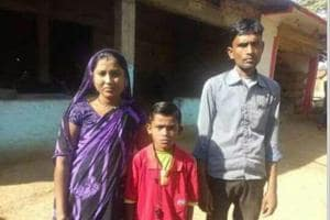 Tushar Uradae with mother Anju and father Santosh outside their house in Kumhari village in Balaghat district of Madhya Pradesh.