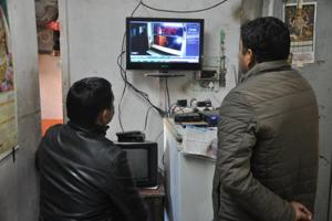 Police personnel check the CCTV footage in connection with the body of a youth that was found in the heart of Dehradun on Monday.