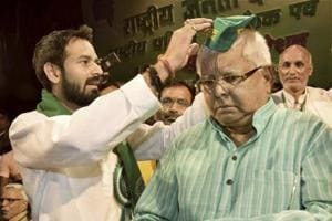 RJD leader Tej Pratap Yadav offers a cap to party chief and his father Lalu Prasad on being re-elected as party president during the party