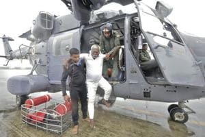 A fisherman who was adrift in the Arabian Sea is escorted down from an Indian Navy helicopter in Thiruvananthapuram after being rescued.