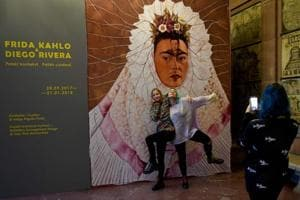 Young visitors take pictures at the entrance of the exhibition on the famed Mexican married Mexican couple Frida Kahlo and Diego Rivera at the ZAMEK Culture Centre in Poznan, Poland.