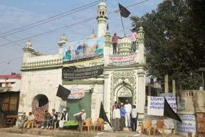 Muslims hoist black flags on a mosque on the 25th anniversary of the Babri Masjid demolition in Ayodhya on Wednesday.