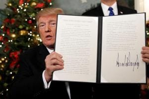 US President Donald Trump holds up the proclamation that announces the United States recognising Jerusalem as the capital of Israel and moving its embassy there, during an address from the White House in Washington.