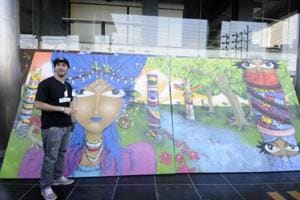 Renowned Brazilian graffiti artist Michael Devis alongside one of his works displayed at KK Modi Education Group Institute in Noida on Thursday.