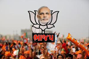 A supporter holds up a cutout of a lotus, the election symbol of BJP, with an image of Prime Minister Narendra Modi during a campaign meeting addressed by Modi ahead of Gujarat state assembly election in Kalol.