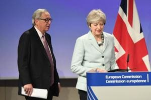 British Prime Minister Theresa May (R) and European Commission President Jean-Claude Juncker arrive to address a press conference at the European Commission in Brussels on December 8, 2017.