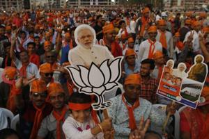 A girl holds cut out of Indian Prime Minister Narendra Modi during an election campaign rally in Ahmadabad on December 8.