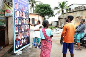 People check the photos of fishermen who have not returned after venturing into the sea at Poonthura coast in Thiruvananthapuram, Kerala, on Saturday.