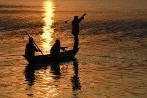 Fishermen at the Brahmaputra river during sunset in Guwahati.