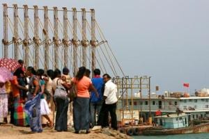 A file photo of a group of Sri Lankan visitors at the new deep water shipping port watch Chinese dredging ships work in Hambantota on March 24, 2010.