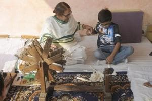 A child learns how to use the charka, or the spinning wheel, to weave a clothe. It was popularised by Mahatma Gandhi.