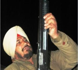 A policeman with a gun that was recovered from the spot where the shooting took place at Khaparkheri village near Amritsar on Wednesday