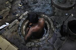 A municipal worker attempts to unblock a sewer overflowing with human excreta in New Delhi in 2009. The practice was banned in 2013.