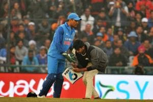 An Indian fan ran on to the field and touched MS Dhoni's feet during the Mohali ODI against Sri Lanka.