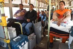 Officials travel on a bus with Electronic Voting Machines and Voter Verifiable Paper Audit Trail (VVPAT) ahead of the second phase of Gujarat Vidhan Sabha elections in Ahmedabad on Wednesday.