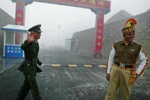 A Chinese soldier stands next to an Indian counterpart at the Nathu La border crossing between India and China in Sikkim state.