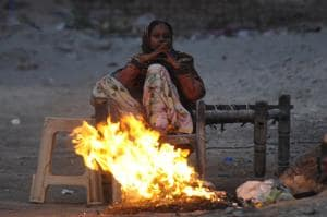A woman warms herself from the cold beside a fire.