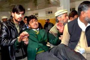 Pakistani volunteers carry a student injured inTaliban attack on the Army Public School in Peshawar, Pakistan.