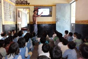 Students listen with rapt attention as a teacher at the Samanpur Jadho government primary school takes classes with the help of a 36-inch LED television set.