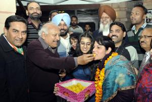 Health Minister Brahm Mohindra offering sweets to Sunaina Choudhary for her victory in ward no 9 during the MC election in Patiala on Sunday.