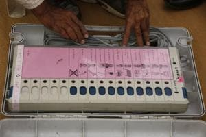 A polling official checks an electronic voting machine at a dispatch center before proceeding to his allotted station for the second phase of voting for the Gujarat assembly elections in Ahmedabad.