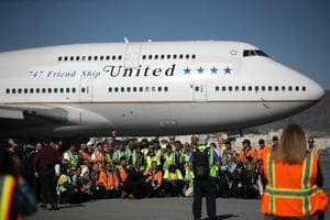 United Airlines workers pose for a photo in front of United Airlines flight 747 before taking off from San Francisco International Airport for its final flight to Honolulu, Hawaii on November 7.