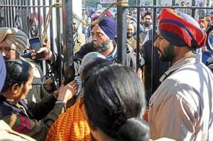 Former mayor Amarinder Singh Bajaj of the SAD argue with police during MC elections in Patiala on Sunday.