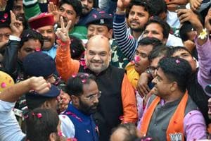BJP president Amit Shah flashes victory sign on his arrival at the party office in New Delhi, after winning assembly elections in Gujarat and Himachal Pradesh.